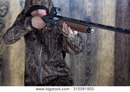 Hunter In Camouflage Clothing With A Gun On Wooden Background. The Man With The Shotgun. Young Guy I