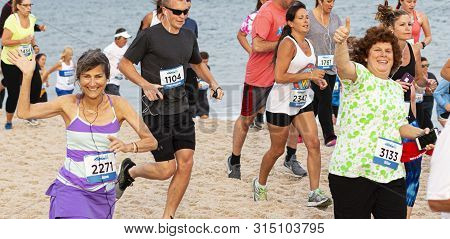 Babylon, New York, Usa - 24 June 2019: Two Women Wave And Give Thumbs Up While Running A Crowded One
