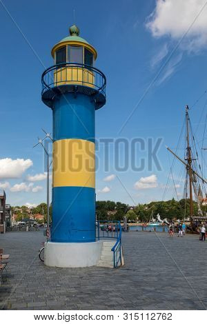 Eckernförde, Germany – July 18, 2019: The historic defunct lighthouse at the harbor, old sail ship at the pier, tourists walking around.