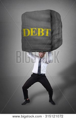 Composite Image. Stress Pressure Of Debt In Business Concept. Businessman Holding Heavy Stone Of Deb