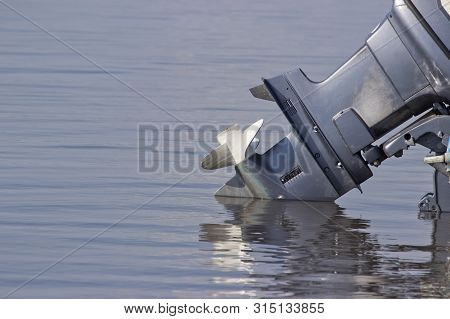 Outboard Motor Lowered Into The Water. A Boat Engine Is Waiting To Be Started.