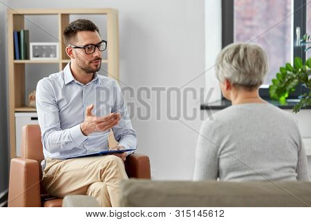 geriatric psychology, mental therapy and old age concept - psychologist talking to senior woman patient at psychotherapy session