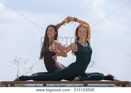 Two Pretty Women Stretching In A Park Before Starting A Workout Session - Girls Doing Gymnastics Exe
