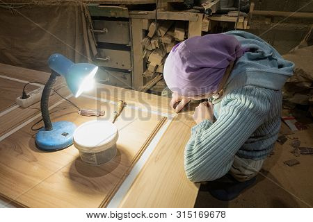 Woman joiner cleans  and putty spats surface of door leaf in the carpentry shop. Woman working in the male profession. poster