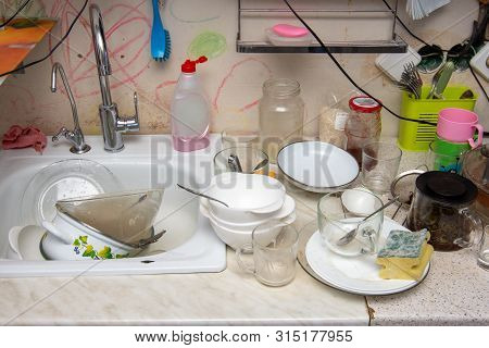 Unwashed Dishes On The Table Of The Old Kitchen