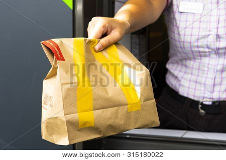 Sankt-petersburg/russia - July 11 2019: Mcdonalds Worker Holding Bag Of Fast Food. Hand With A Paper