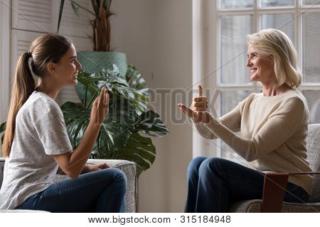 Grown Up Daughter Talk With Elderly Mother Using Sign Language