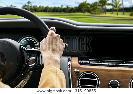 Woman's Hands On The Steering Wheel Driving Modern Luxury Car. Concept Woman Driving. Hands Holding