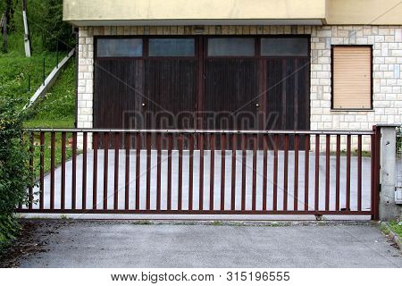 Paved suburban family house driveway leading towards closed metal fence doors and garage surrounded with uncut grass on warm sunny summer day poster
