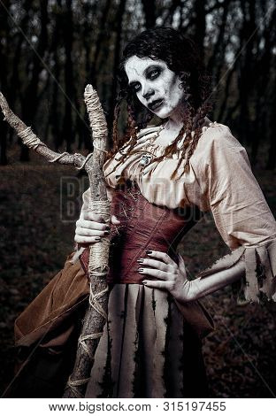 Halloween Theme: Gloomy Creepy Voodoo Witch With Stick. Portrait Of The Evil Hex In Dark Forest. Zom