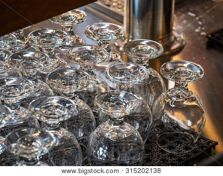 Rows Of Beer Snifters Glasses Resting On A Bar Ready For Serving