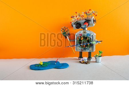 Fishing And Vacation Robotic. Robot Angler With Fishing Rod Catches Fish In A Pond. Blue Lake, Water