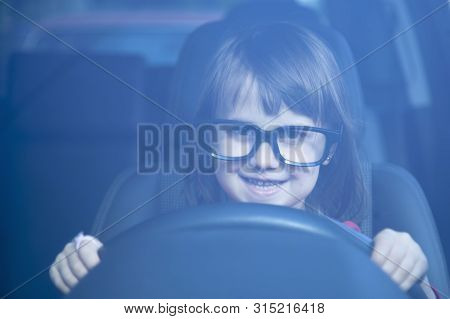 Driving Shool. Happy Cute Little Child Girl Learns To Drive. Humorous Photo.