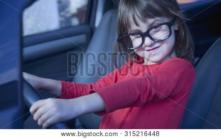 Driving Shool. Humorous Photo Of Happy Cute Little Child Girl In Glasses Learns To Drive.
