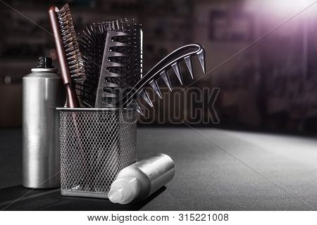 Flacons Of Professional Hair Sprays Near A Metal Basket With Combs Standing On A Table In A Salon. C
