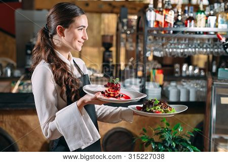 Waiter Serving In Motion On Duty In Restaurant. The Waiter Carries Dishes.