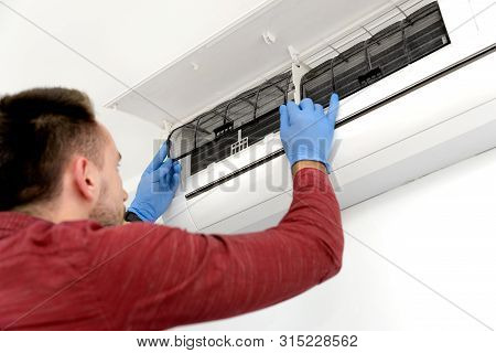 Technician Repairing Air Conditioner Appliance. Young Man Takes Care Of The Cleanliness Of The Air-c