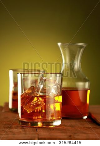 Chilled Whisky Glass With Ice Cubes On Amber Background