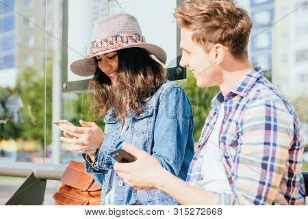 Two Laughing People Chatting At Bus Stop. Couple Traveler Waiting For Tram On Stop Outdoor With Smar