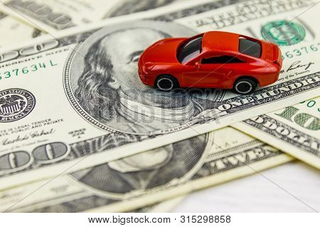 American Dollars And Miniature Car Model On White Wooden Background. Car Loan Concept