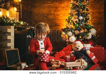 Family Holiday. Childhood Memories. Santa Boy Celebrate Christmas At Home. Boy Child Play Near Chris