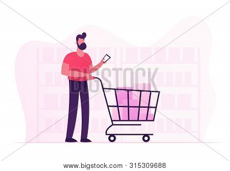 Customer Stand In Grocery Or Supermarket With Goods In Shopping Trolley Holding Smartphone In Hand.