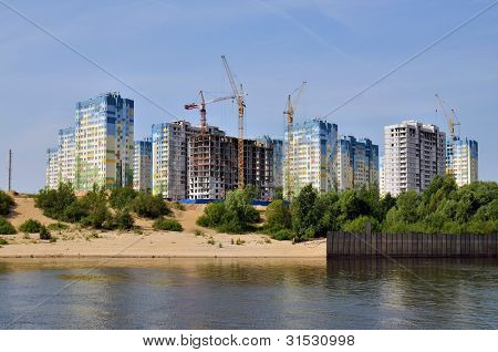 Block of flats and buildings under construction on river bank poster