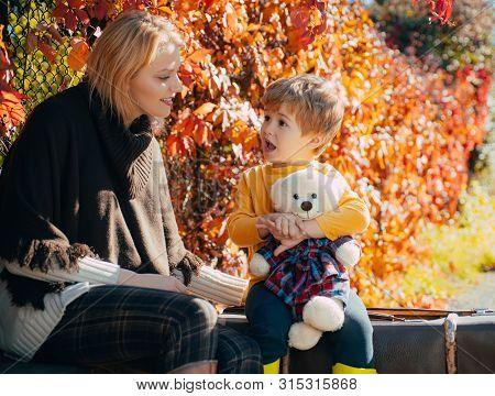 Mom Little Son Communicate Autumn Foliage Background. Trustful Relations. Parenthood And Upbringing.