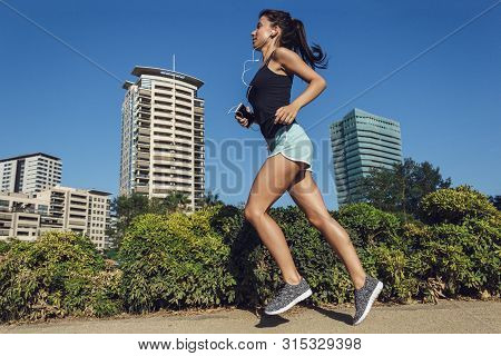 Beautiful Fitness Girl Running In The City. Female Running On Sidewalk With Urban Background Of Skys