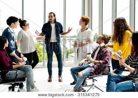 Attractive Young Multiethnic Group Talking At Relax Zone In Coffee Break Time At Office. Young Asian