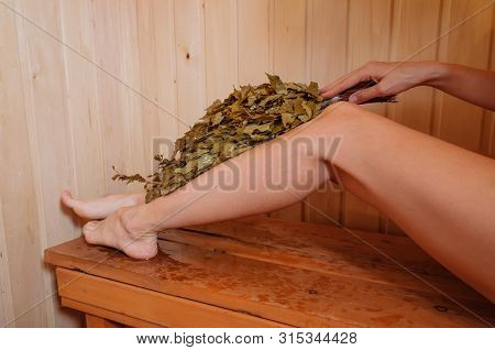 Female Legs On A Wooden Bench In The Bath. In The Hand Is A Birch Broom For Steaming. The Concept Of