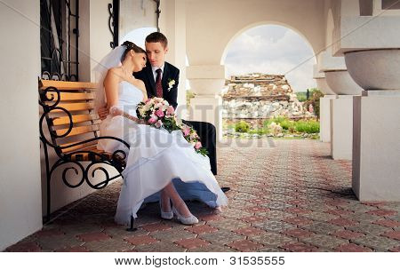 The bride and groom sitting on a bench