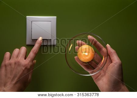 Female Hand With Burning Candle And Female Finger Turns Of Light Switch On The Green Background. Int