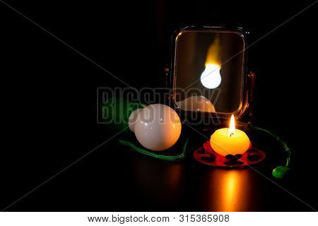 Mirror With Reflection Of The Burning Lamp, Green Non Burning Bulb With Rope And Burning Yellow Cand