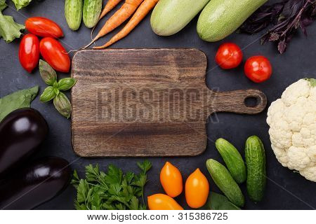 Assorted Raw Organic Vegetables And Cutting Board On Dark Stone Background Harvest Time Vegetarian E