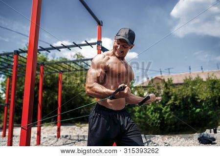 Fitness Man Training Chest With Resistance Bands At Street Gym Yard. Strength And Motivation. Outdoo