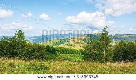 Beautiful Countryside In Mountain. Sunny Weather. Clouds On The Blue Sky
