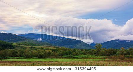Wonderful Landscape Of Rural Area At Dawn. Amazing Cloudscape Above The Mountain Ridge.  Overcast Au