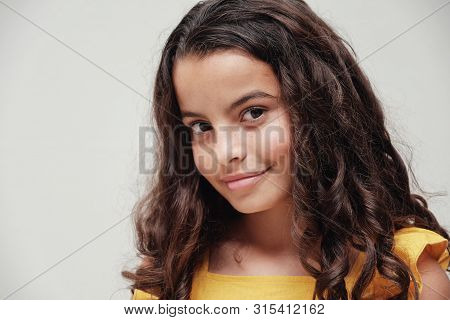 Close Up Portrait Of A Confident And Gorgeous Mixed Multicultural Preteen Girl With Beautiful Curly