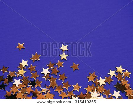 Golden Stars Glitter On Violet Background. Festive Holiday Bright Backdrop