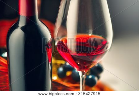 Red wine. Wine. Bottle and glass of Red wine with ripe grapes still life. Red wine Over black background. Angle art design with space for your text. Vintage styled