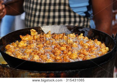 Man Frying Spicy Snack Or Entree Dish Similar To A Fritter, B On Street.
