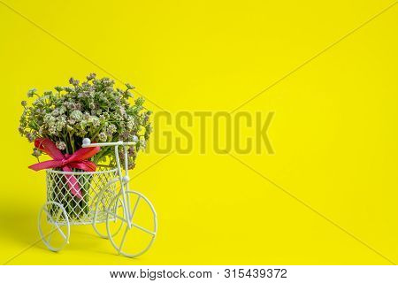 A Toy Bike Carries A Flowers. The Idea For A Postcard. Yellow Background. Minimalism