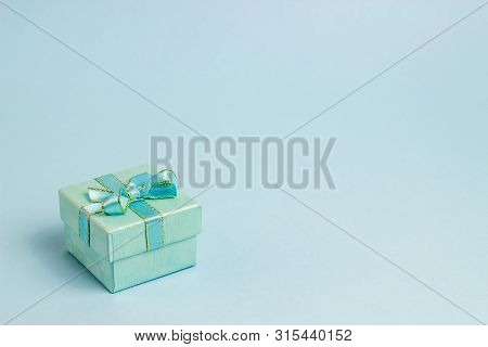 Gift Box On A Blue Background. The Idea For A Postcard. Minimalism.