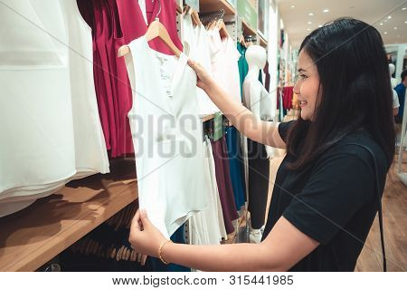 Consumerism and Beauty Women Fashion Shopping Concept, Portrait of Pretty Woman is Looking for New Clothes and Choosing  in Shopping Department Store., Shopaholic Lifestyles and Leisure Activities.
