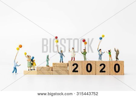 Miniature People : Happy Family Holding Balloon On Wooden Block Number 2020  , Happy New Year Concep