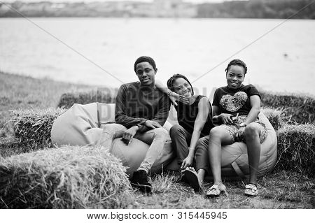 Three African American Friends Chill And Sitting On Poufs Outdoor.