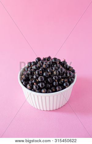 Ripe Black Currant Or Blueberries In A Small White Cup On A Pink Background. Black Currant Harvest.