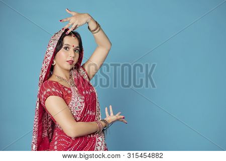 Studio Portrait Of Young Woman In Traditional Indian Sari Dress Wearing Bracelets And Nose Ring When