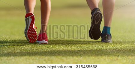 Couple Runners Athletes Feet Running On Grass. Female Y Male Fitness Sunlight Jogging Workout. Sport